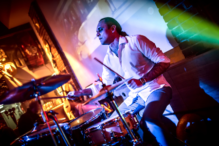 Drummer playing on drum set on stage. Warning - authentic shooting with high iso in challenging lighting conditions. A little bit grain and blurred motion effects. Stock Photo - 75712999