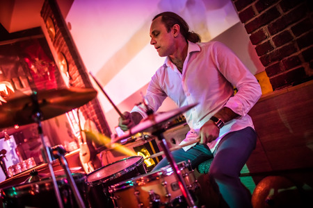 Drummer playing on drum set on stage. Warning - authentic shooting with high iso in challenging lighting conditions. A little bit grain and blurred motion effects. Stock Photo - 75713052