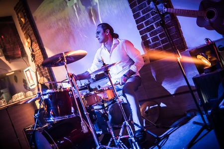 Drummer playing on drum set on stage. Warning - authentic shooting with high iso in challenging lighting conditions. A little bit grain and blurred motion effects. Stock Photo - 75713077