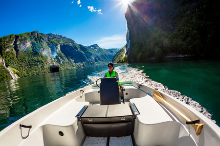 Woman driving a motor boat. Geiranger fjord, Beautiful Nature Norway.Summer vacation. photo