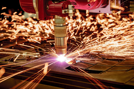 poquito: CNC Laser plasma cutting of metal, modern industrial technology. . Small depth of field. Warning - authentic shooting in challenging conditions. A little bit grain and maybe blurred. Foto de archivo
