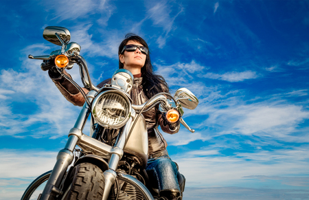 Biker girl in a leather jacket on a motorcycle photo