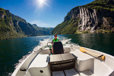 Woman driving a motor boat. Geiranger fjord, Beautiful Nature Norway. Summer vacation. photo