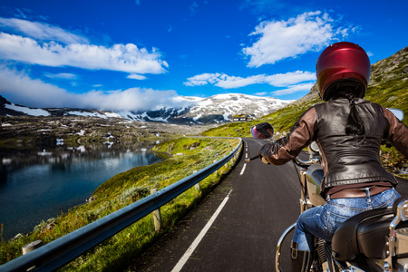 Biker girl rides a mountain road in Norway. First-person view. photo