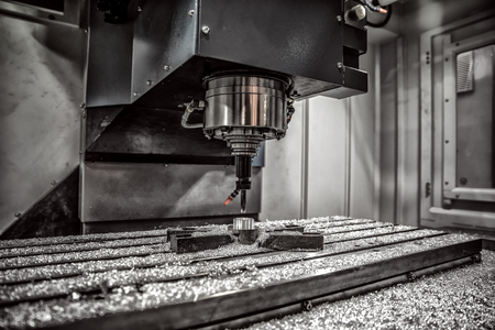maybe: Metalworking CNC milling machine. Cutting metal modern processing technology. Small depth of field. Warning - authentic shooting in challenging conditions. A little bit grain and maybe blurred.