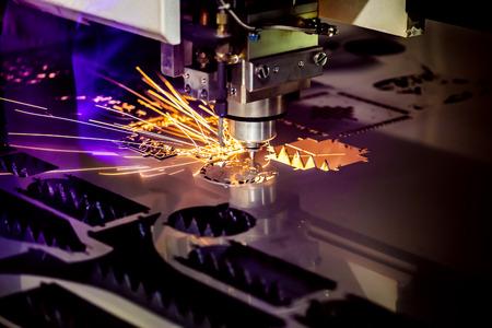 CNC Laser snijden van metaal, moderne industriële technologie. Kleine scherptediepte. Waarschuwing - authentieke opname in moeilijke omstandigheden. Een beetje graan en misschien wazig. Stockfoto - 78593872