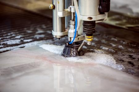 CNC water jet cutting machine modern industrial technology. Фото со стока