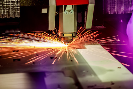 poquito: CNC Laser cutting of metal, modern industrial technology. Small depth of field. Warning - authentic shooting in challenging conditions. A little bit grain and maybe blurred.