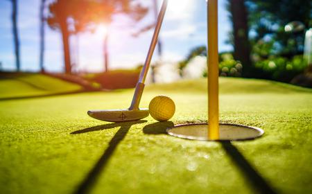 석양에 구멍 근처 박쥐와 미니 골프 노란색 공