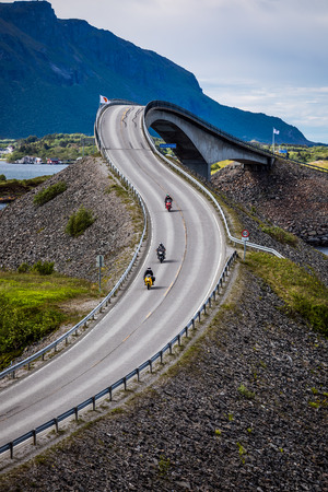 Three bikers on motorcycles. Atlantic Ocean Road or the Atlantic Road (Atlanterhavsveien) been awarded the title as Norwegian Construction of the Century.