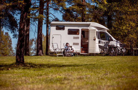 Woman looking at the laptop near the camping . Caravan car Vacation. Family vacation travel, holiday trip in motorhome. Wi-fi connection information communication technology.
