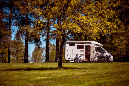 Woman looking at the laptop near the camping . Caravan car Vacation. Family vacation travel, holiday trip in motorhome RV. Wi-fi connection information communication technology. Stock Photo