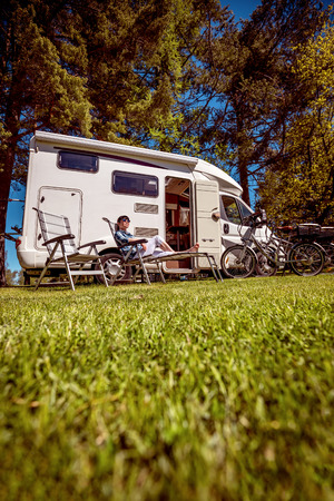 Woman resting near motorhomes in nature. Family vacation travel, holiday trip in motorhome RV, Caravan car Vacation. Stock Photo - 87327526