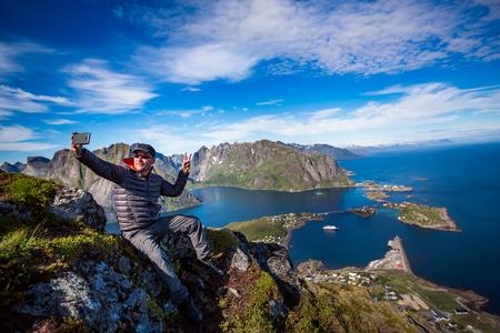 Man on top of a mountain taking a selfie in Norway Lofoten archipelago islands.