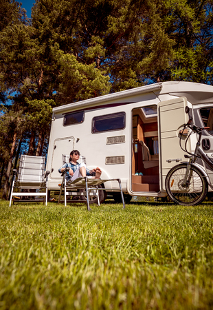 Woman resting near motorhomes in nature. Family vacation travel, holiday trip in motorhome RV, Caravan car Vacation. Stock Photo - 87327531