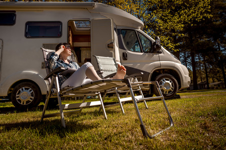 Woman resting near motorhomes in nature. Family vacation travel, holiday trip in motorhome RV, Caravan car Vacation. Stock Photo - 90412777
