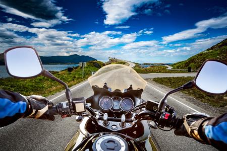 Biker monta un camino con Atlantic Ocean Road en Noruega. Vista en primera persona.