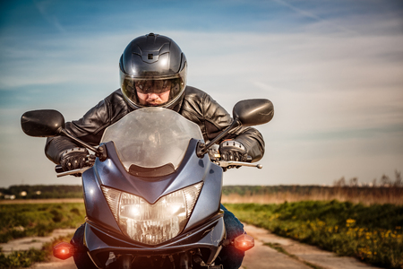 Biker in helmet and leather jacket racing on the road Archivio Fotografico