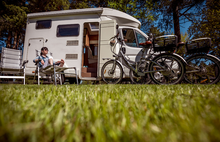 Woman resting near motorhomes in nature. Family vacation travel, holiday trip in motorhome RV, Caravan car Vacation. Stock Photo - 93412277