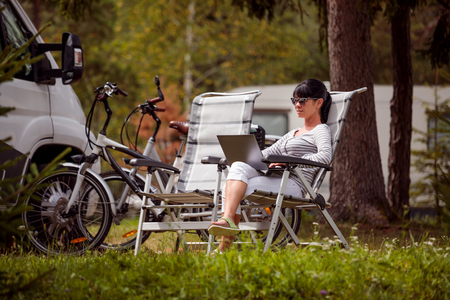 Woman looking at the laptop near the camping . Caravan car Vacation. Family vacation travel, holiday trip in motorhome RV.  connection information communication technology. Stock Photo