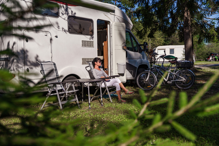 Woman resting near motorhomes in nature. Family vacation travel, holiday trip in motorhome RV, Caravan car Vacation. Stock Photo - 94065950