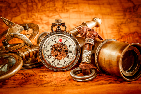 Vintage compass, magnifying glass, pocket watch, quill pen on an old ancient map in 1565. Vintage still life. Stock Photo