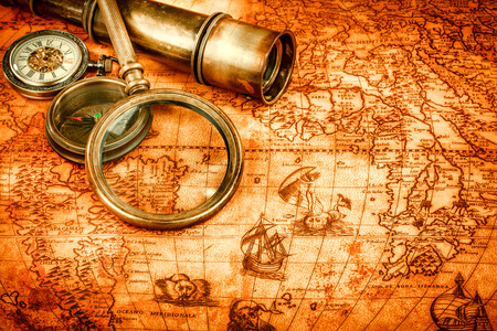 Vintage compass, magnifying glass, pocket watch, quill pen on an old ancient map in 1565. Vintage still life.