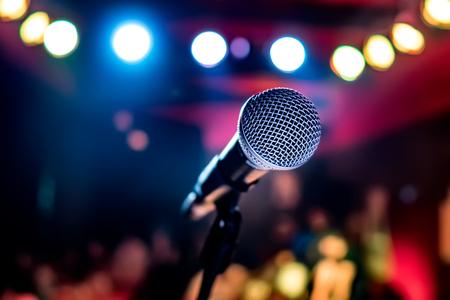 Actuación pública en el escenario Micrófono en el escenario en un contexto de auditorio. Poca profundidad de campo. Actuación pública en el escenario. Foto de archivo