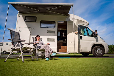 Woman resting near motorhomes in nature. Family vacation travel, holiday trip in motorhome RV, Caravan car Vacation. Stock Photo - 95829707