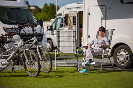 Woman resting near motorhomes in nature. Family vacation travel, holiday trip in motorhome RV, Caravan car Vacation.