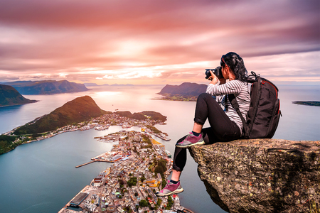 Nature photographer tourist with camera shoots while standing on top of the mountain. Aksla at the city of Alesund , Norway. Stock Photo