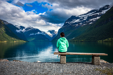 Beautiful Nature Norway natural landscape. lovatnet lake. The woman on the bench at the lake admires the beautiful view.