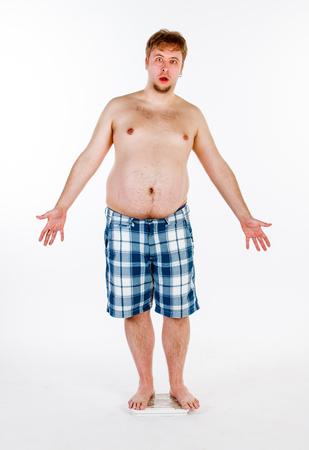 Hombre gordo y gordo que se pesa en escalas.