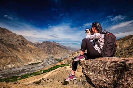 Dhankar gompa. Spiti Valley, Himachal Pradesh, India. Nature photographer tourist with camera shoots while standing on top of the mountain. Stock Photo