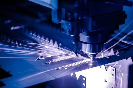 Taglio laser CNC di metallo, moderna tecnologia industriale. Piccola profondità di campo Avvertenza: riprese autentiche in condizioni difficili.
