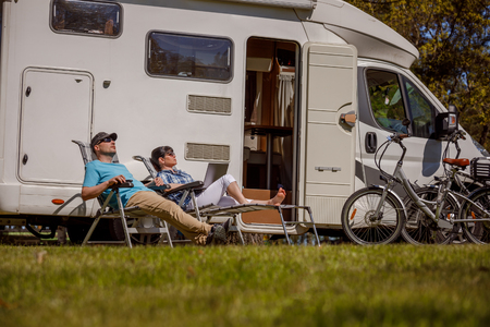 Woman with a man resting near motorhomes in nature. Family vacation travel, holiday trip in motorhome RV, Caravan car Vacation. Stock Photo - 108097541