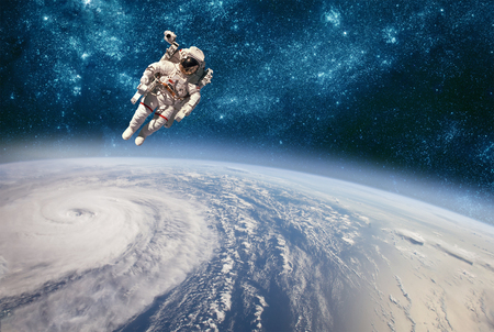 Astronaut in outer space against the backdrop of the planet earth. Typhoon over planet Earth. Banco de Imagens