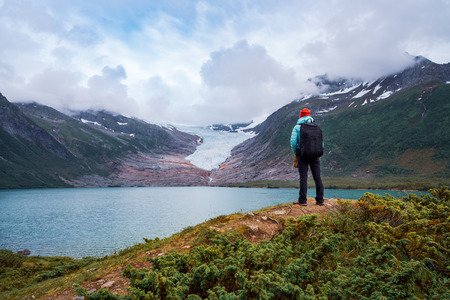 Girl tourist looks at a glacier. Svartisen Glacier in Norway. Beautiful Nature Norway. Stock Photo