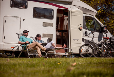 Woman with a man resting near motor homes in nature.