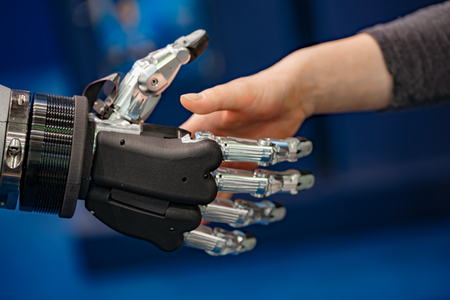 Hand of a businesswoman shaking hands with a   robot. Stock Photo