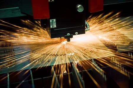 Découpe laser CNC de métal, technologie industrielle moderne. Petite profondeur de champ. Attention - tir authentique dans des conditions difficiles. Banque d'images