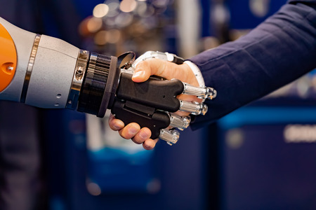 Hand of a businessman shaking hands with a   robot. 版權商用圖片