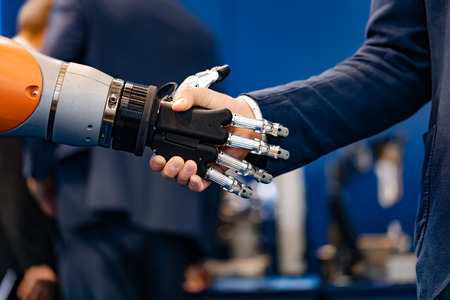 Hand of a businessman shaking hands with a robot