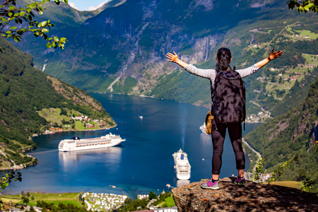 Girl standing at the cliff overlooking Geiranger Fjord Beautiful Nature Norway 写真素材 - 125020145