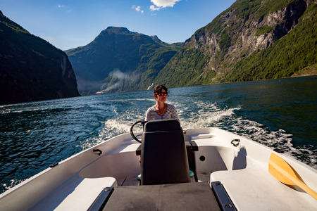 Woman driving a motor boat. 写真素材 - 125020159