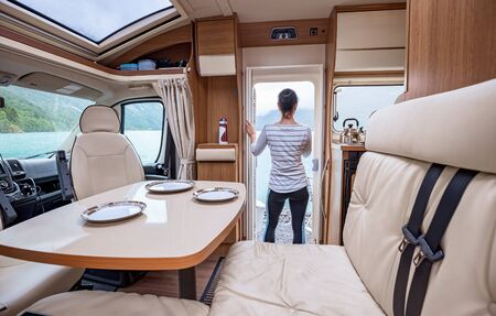 Woman in the interior of a camper RV motorhome with a cup of coffee looking at nature. 写真素材 - 128817212