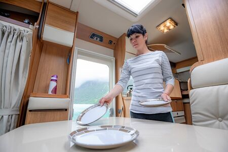 Woman cooking in camper, motorhome RV interior. Family vacation travel, holiday trip in motorhome, Caravan car Vacation. 写真素材 - 128817213