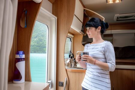 Woman in the interior of a camper RV motorhome with a cup of coffee looking at nature. 写真素材 - 128817239