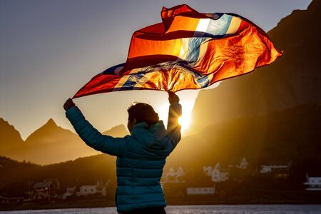 Woman waving the flag of Norway at sunset 写真素材