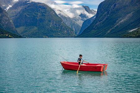 Woman fishing on a boat. Beautiful Nature Norway natural landscape.